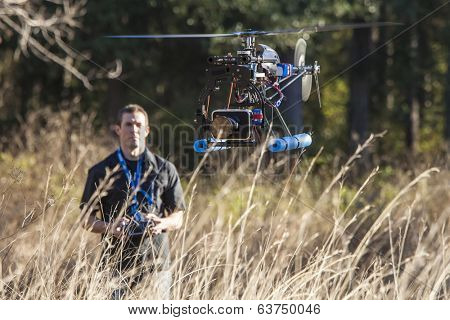 man flying uav helicopter with video camera