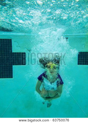underwater view of girl jumping into pool