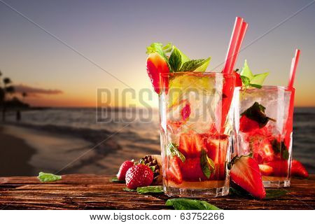 Mojito drinks on wood with evening blur ocean shore background