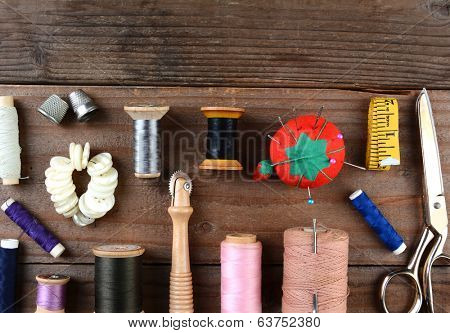 High angle shot of antique sewing tools on a rustic wooden surface. Items include, Thread, scissors, pin cushion, buttons, thimble, tape measure and more.