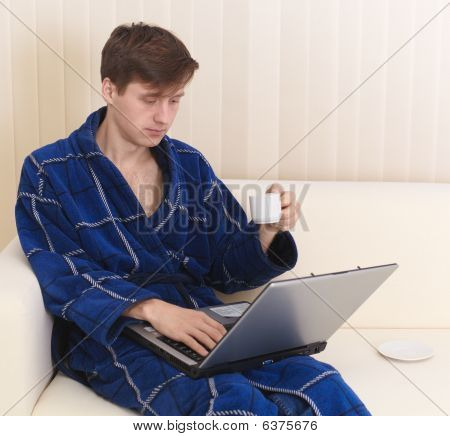 Guy Works In Internet On Sofa And Drinks Coffee