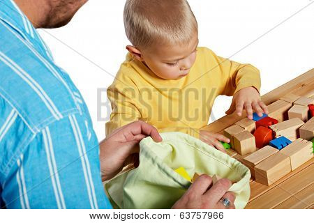 Father and son playing with wooden blocks on studio background