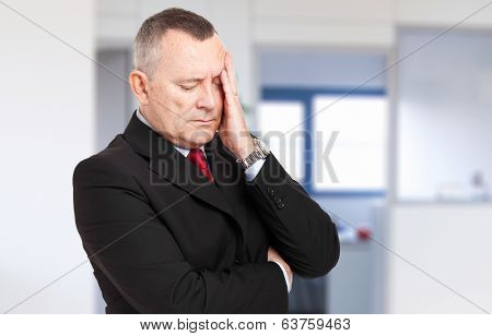 Senior stressed businessman in his office