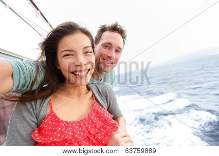 Cruise ship couple taking selfie self portrait photo romantic. Happy lovers, woman and man traveling on vacation travel sailing on open sea ocean enjoying romance. Young Asian woman and Caucasian man.