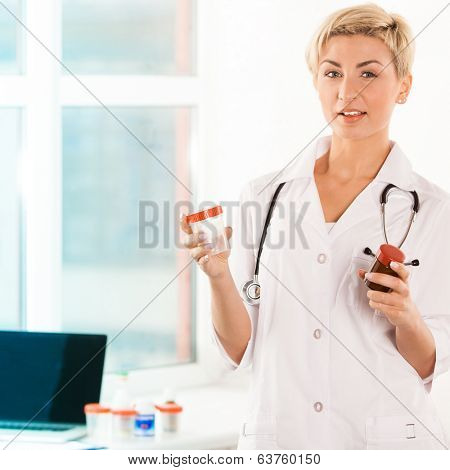 Portrait of a young pharmacist with pills near the window