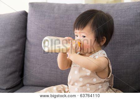 Adorable baby girl drinking milk from bottle