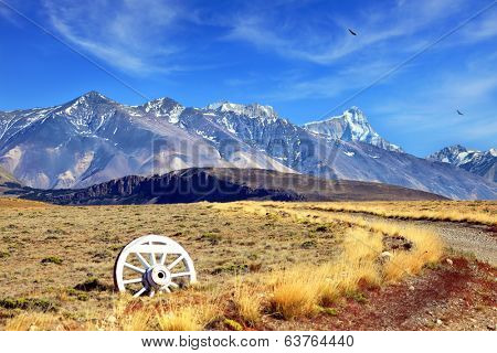 Road sign in the form of a wagon wheel. Gravel road in the desert. In the distance the snow-covered mountains. Argentine Patagonia, Perito Moreno National Park