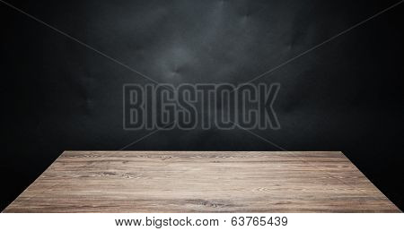 Wooden table top against dark background