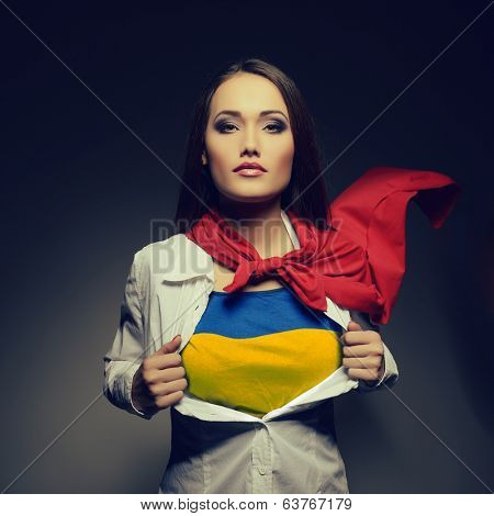 Pretty woman opening her shirt painted in ukrainian flag colors like superhero. Young girl twenty-years-old like Ukraine fights for independence, democracy, peaceful life. Ukrainian patriot concept.