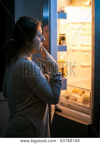 Woman Looking In The Refrigerator At Late Evening
