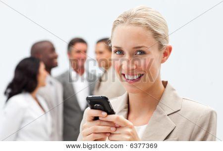 lächelnd geschäftsfrau Schreiben einer Nachricht mit einem Mobiltelefon