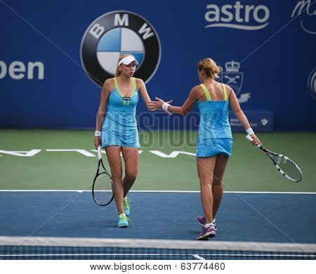KUALA LUMPUR - APRIL 19, 2014: Olga Savchuk and Lyudmyla Kichenok (white cap) get in for motivational handshake in the women's semifinals of the BMW Malaysian Open tennis in Kuala Lumpur, Malaysia.