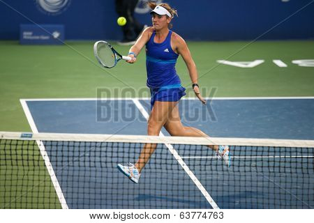 KUALA LUMPUR - APRIL 20, 2014: Timea Babos of Hungary (blue) returns during the doubles final of the BMW Malaysian Open Tennis in Kuala Lumpur, Malaysia. She partners Chan Hao-Ching to emerge winners.