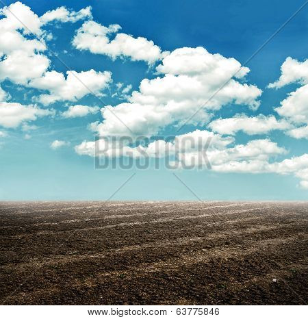 Wide wet soil ways, trails, dry rows outdoor. Natural brown dirty texture of organic and plowed rural land in country farm, prolific rough surface for outside planting on blue cloudy sky in sunny day.