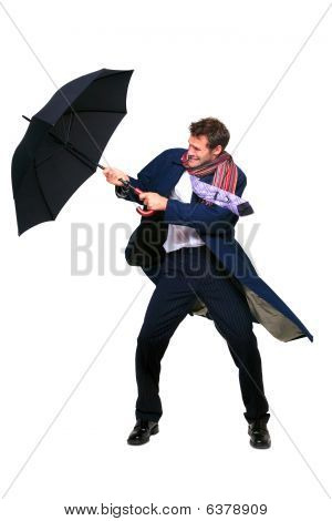 Businessman Struggling With Umbrella