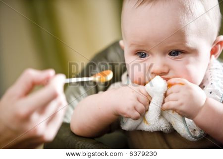 Cute baby eating solid food from a spoon