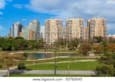 City park with small pond, green lawns and walkways and modern residential buildings on background in Valencia, Spain.