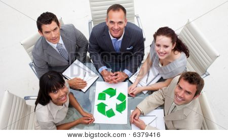 High Angle Of Smiling Business Team Holding A Recycling Symbol