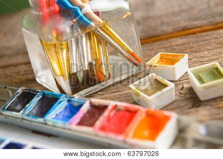 Professional watercolor aquarell paints in box with brushes in jar with water