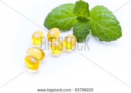 Gel vitamin capsules with mint leaf.