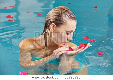 Young woman relaxing in water of swimming pool with red roses