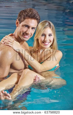 Happy man carrying smiling woman in a swimming pool