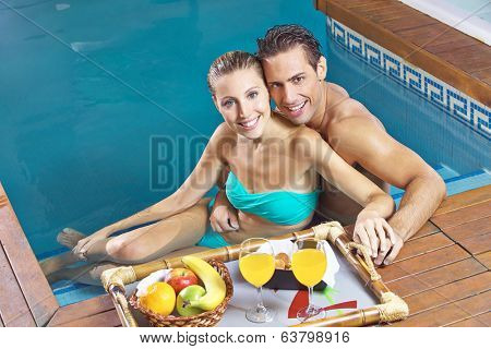 Smiling couple eating breakfast with fruits and juice in a swimming pool