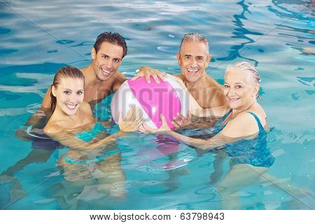 Happy group playing in swimming pool with a water ball in summer