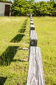 image of split rail fence  - An old wood rail fence running across a green meadow - JPG