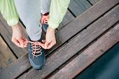 picture of rainy day  - Fitness woman lacing running sport shoes before workout on rainy day - JPG