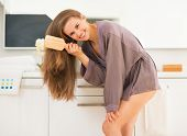 image of peignoir  - Happy young woman combing hair in bathroom - JPG