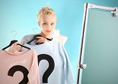 picture of covenant  - A woman stands in front of a mirror and holding a blue and a pink blouse - JPG