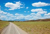 image of trailblazer  - Dirt road in desert leading to the mountains - JPG