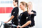 stock photo of contactor  - Female coach giving man and woman ems electro muscular stimulation exercise - JPG
