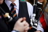 pic of bagpipes  - Color shot of a person holding a traditional bagpipe - JPG