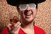 pic of crazy hat  - Crazy rock and rollerer with a big black hat party glasses and a glass of whiskey in front of a cheetah skin background - JPG
