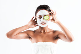 stock photo of mud pack  - Young African woman in Studio doing body care with refreshing cucumber facial mask for young and beautiful skin and relaxation - JPG