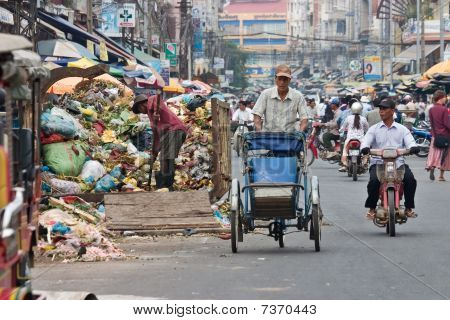 Cyclo driver peddling past garbage