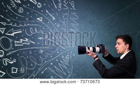 Photographer boy shooting images while energetic hand drawn lines and doodles come out of the camera