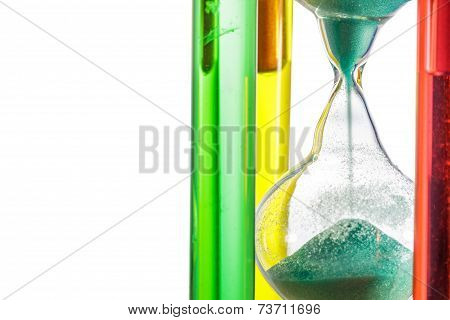 Colorful Hourglass With Green Sand On White Background.