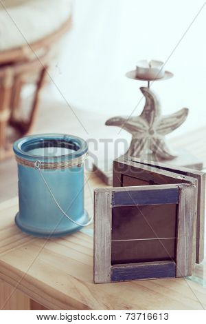 Idea of interior decor in beach cottage style with trendy glass candlestick and rustic photo frame.