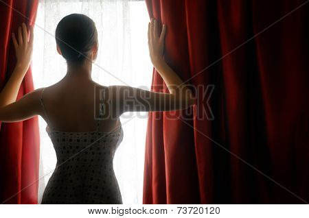 pretty woman opening red curtains