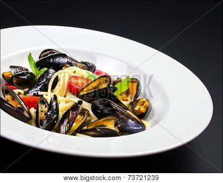Gourmet Mussels With Fresh Italian Pasta, Cherry Tomato And Herbs For A Tasty Seafood Meal Over Blac