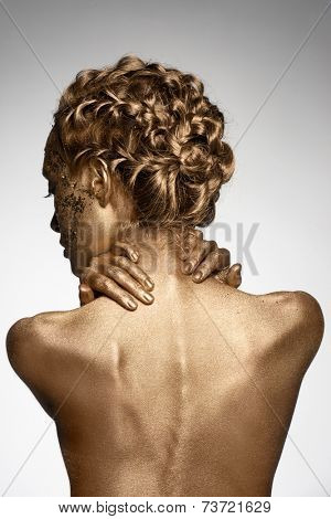 Portrait of beautiful woman with golden bodyart and hairstyle with braids