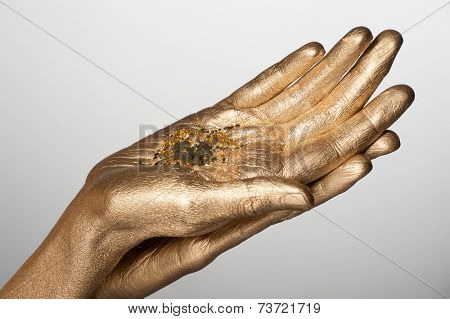 Closeup of woman hands with golden bodyart holding golden sparkles