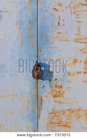 Rusty Blue Metal Gate With Padlock