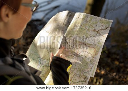 Woman Hiker With Backpack Holding A Map In The Countryside