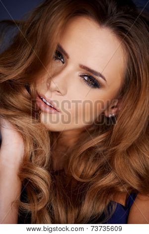 Attractive sensual woman with long curly brown hair gathered around her face looking at the camera with parted lips and a sultry expression