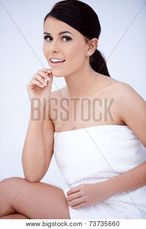 Close up Smiling Pretty Young Woman Wrapped in White Towel on Body Portrait  Looking at Camera. Captured in Studio.