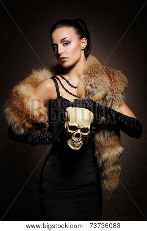 Young, rich and beautiful woman with the scull over the vintage background